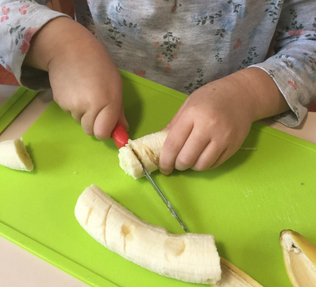 Child cutting banana